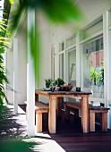 Moderne, rustikale Holztischgarnitur auf überdachter Terrasse am Wohnhaus