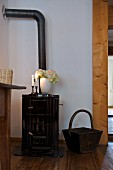 Vase of flowers and lit candles on old wood-burning stove in renovated house