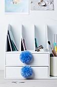 Pompoms decorating drawers of desk filing trays