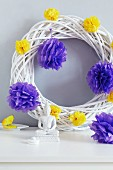 White wicker wreath decorated with tissue paper pompoms