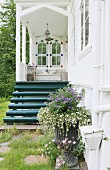 Eingangsbereich mit nostalgischer weißer Veranda und petrolfarber Holztreppe, davor bepflanzte Amphore