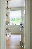 Elegant, white country-house kitchen with parquet floor, white wooden ceiling and chandelier