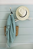 Summer hat, scarf and bag hanging on nostalgic coat pegs on pale blue wall panelling