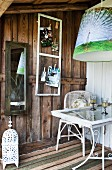 Pictures pegged to chicken wire and mirror on wall next to chair and table on rustic wooden terrace