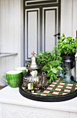 Sage, basil and silver teapot on tiled mosaic tray