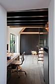 Arbeitszimmer unter dunkler Balkendecke mit grüner Vintage-Leiter und einem grauen Einbauschrank