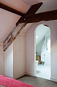 Rustic roof beams in bedroom with fitted wardrobe under sloping ceiling and ensuite bathroom