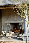 Veranda with columns, fire in large open fireplace and vintage table and chairs