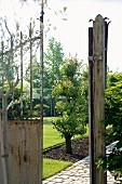 View through rusty gate into well-tended garden with paved path