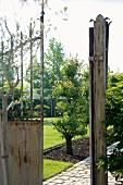 Blick durch rostiges Tor in gepflegten Garten mit gepflastertem Gartenweg