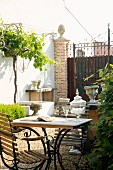 Garden table with marble top and pretty garden chairs next to deciduous hedge; large closed iron gate in background