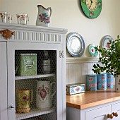 Old, white-painted china cupboard with wire mesh door panel and romantic, floral crockery decorating country-house kitchen