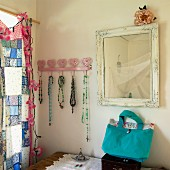 Vintage mirror and strings of beads on pink coat rack with heart motif next to window with patchwork curtain and garland of floral fairy lights