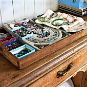 Boxes of colourful beads and necklaces on tray on old wooden cabinet