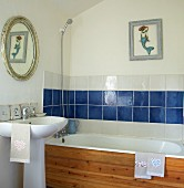 Wood-clad bathtub in small bathroom with picture of mermaid above blue and white tiles