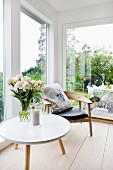 Side table with white, round top and retro wooden chair on pale wooden floor next to large windows