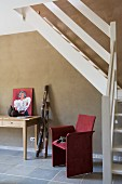 White-painted wooden staircase against grey wall and red-covered chair next to console table in modern foyer