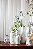Sammlung strukturierter, weisser Porzellanvasen mit zarten Frühlingsblumen