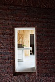 View through opening in brick facade of modern counter in wood-panelled room