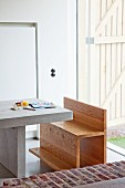 Wooden bench at concrete table in front of wooden board terrace door