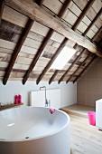Round bathtub in modern attic bathroom with wooden ceiling