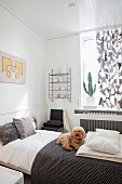 Poodle on houndstooth blanket in cheerful guest bedroom in soft shades of grey