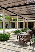Terrace area under shady pergola with white, round columns, small tables and inviting armchairs for relaxing