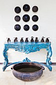 Collection of vintage miniature vehicles on blue console table below objet d'art on wall