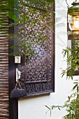 Carved wooden panel on house facade and lantern hanging on tree