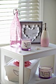 Scented candle, soap dispenser, maritime ornaments and swing-top bottle on bathroom cabinet