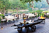 Restaurant terrace with buffet on rustic, agricultural trailer and set tables against backdrop of river landscape