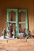 Ethnic, metal busts and vintage door panels on wooden trunk against wall