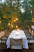 Festively set, candlelit table in twilight garden