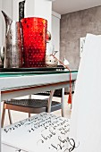 Original vessels on tray on modern dining table and calligraphy on chair seat