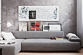 Seating area in harmonious shades of grey with chaise sofa and calligraphy on marbled wall