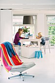 Two children with laptop and toys sitting in cool, white dining area; colourful striped towel on swivel chair in foreground