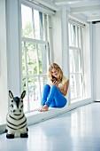 Junges Mädchen in weißem Raum am Fenster sitzend; Spielzeugtier im Vordergrund