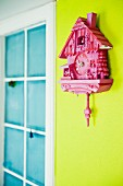 Pink cuckoo clock on spring green wall
