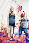Two little girls playing dress-up on blue and red kilim rug; attic room with white-painted wood panelling