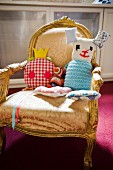 Imaginative, hand-sewn soft toys on old upholstered armchair