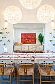 White dining table with wooden inlays and classic, 50s chairs; painting in niche in background