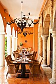 Colonial-style dining area with impressive metal chandeliers between stone columns