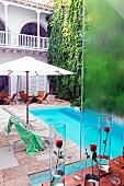 Red roses in glass vases on table and view down onto pool with loungers under parasols in colonial-style hotel courtyard