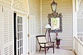 Antique armchair on white veranda; open lattice door with rounded arch above