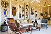 Vintage leather rocking chair and rattan sofa set in lounge amongst handcrafted artworks hanging on wooden wall