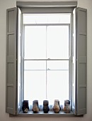 Window with pale grey interior shutters and collection of vases on windowsill