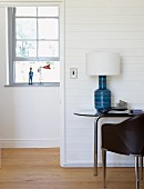 Chair in front of table lamp with white lampshade on side table next to open door with view of window