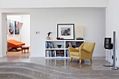 50s armchair and half-height shelving unit on concrete platform with steps and view of orange sofa through open door