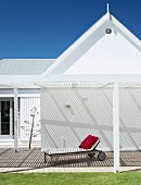 Sun lounger under white pergola attached to gable facade of angular house