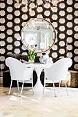 weiße Kunststoffstühle (Phillipe Starck) mit weißem Bistrotisch vor braunem Sofa und kreisfömiger Spiegel an Wand mit gemusterter Tapete